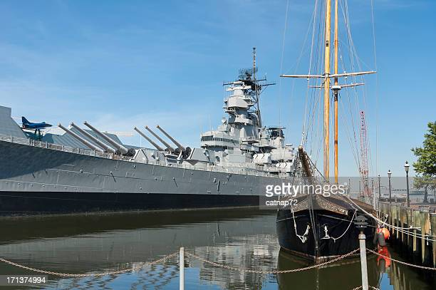 uss wisconsin battleship and old wooden sailing boat - norfolk virginia stock photos and pictures