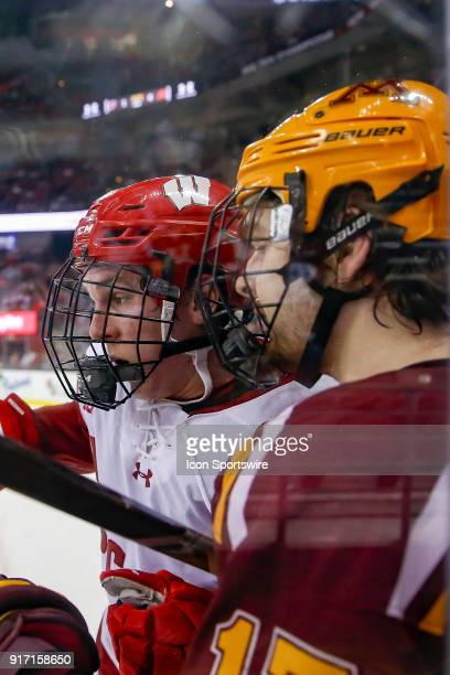 Wisconsin center Seamus Malone and Minnesota forward Tommy Novak against the glass during a college hockey match between the University of Wisconsin...