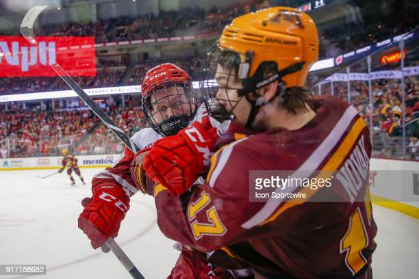 Wisconsin center Seamus Malone pushes Minnesota forward Tommy Novak into the glass during a college hockey match between the University of Wisconsin...