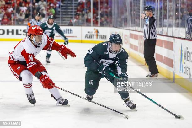 Wisconsin defenseman JD Greenway chases Michigan State right wing Mitchell Lewandowski into the corner during a college hockey match between the...