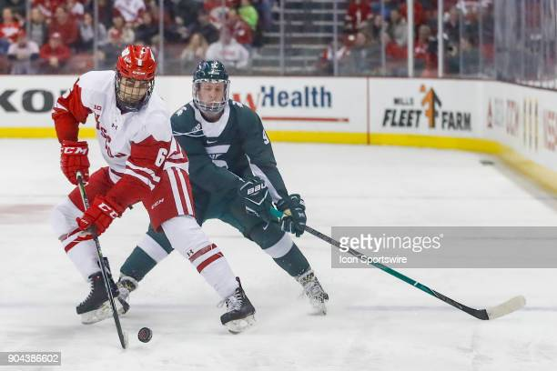 Wisconsin defenseman Peter Tischke and Michigan State right wing Mitchell Lewandowski battle for the puck during a college hockey match between the...