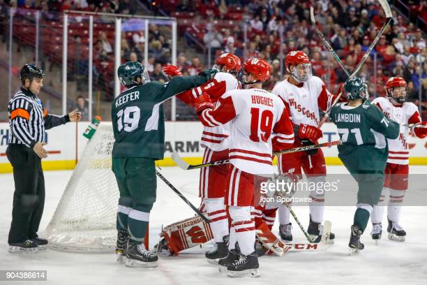 Wisconsin defenseman Tyler Inamoto and Michigan State right wing David Keefer mix it up in front of the Wisconsin goal during a college hockey match...