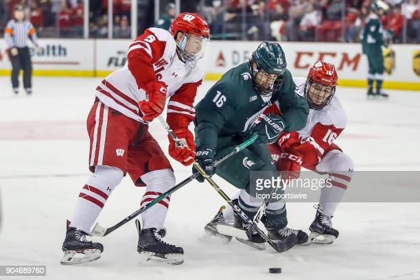 Wisconsin defenseman Tyler Inamoto and Wisconsin center Tarek Baker work to get the puck from Michigan State right wing Brody Stevens during a...