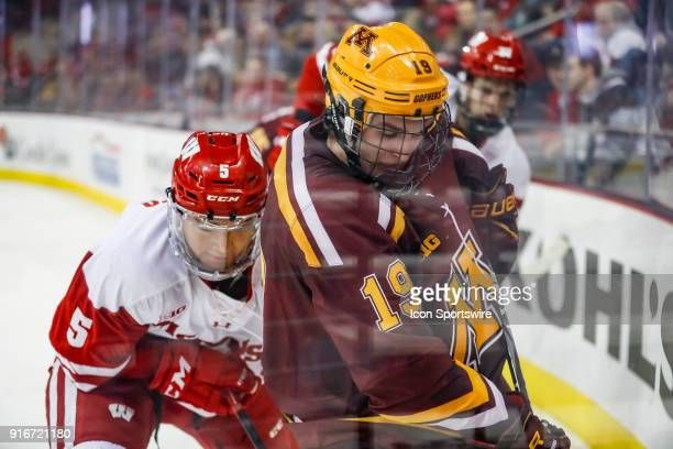 Wisconsin defenseman Tyler Inamoto checks Minnesota forward Scott Reedy into the boards during a college hockey match between the University of...