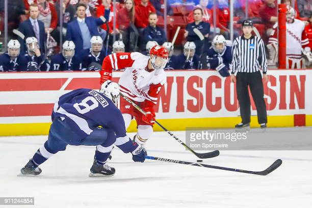 Wisconsin defenseman Tyler Inamoto looks to pass the puck past Penn State forward Chase Berger during a college hockey match between the University...