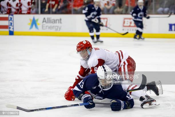 Wisconsin defenseman Tyler Inamoto tries to pin Penn State forward Nikita Pavlychev to the ice during a college hockey match between the University...