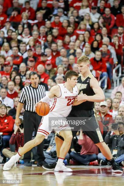 Wisconsin forward Ethan Happ is guarded by Purdue center Isaac Haas during a college basketball game between the University of Wisconsin Badgers and...