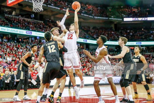 Wisconsin forward Ethan Happ puts up a shot over Purdue center Isaac Haas during a college basketball game between the University of Wisconsin...