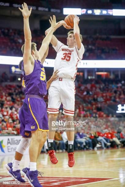 Wisconsin Forward Nate Reuvers shoots over Northern Iowa Forward Austin Phyfe during an NCAA basketball game between the University of Wisconsin...