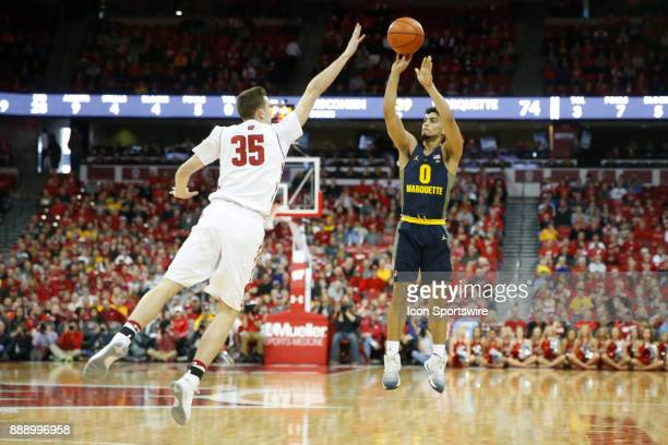 Wisconsin forward Nate Reuvers tries to keep Marquette guard Markus Howard from scoring during a college basketball game between the University of...