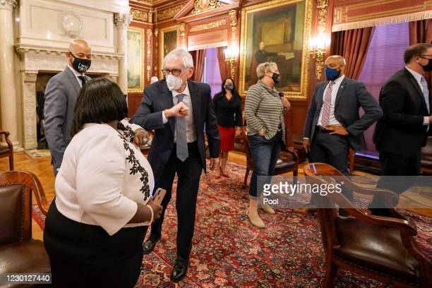 Wisconsin Gov. Tony Evers elbow bumps a member of Wisconsin's Electoral College after they all cast their votes for the presidential election at the...