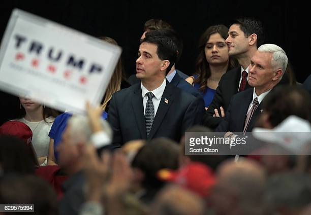Wisconsin Governor Scott Walker , Paul Ryan , speaker of the U.S. House of Representatives, and Vice President-Elect Mike Pence listen as...