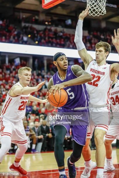 Wisconsin guard TJ Schlundt reaches in while Wisconsin forward Ethan Happ tries to block Northwestern center Dererk Pardon during a college...