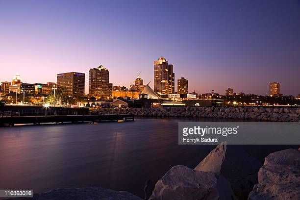 USA, Wisconsin, Milwaukee skyline across lake at dusk