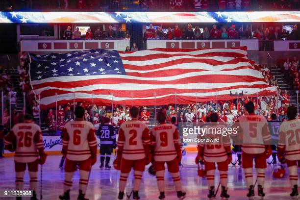 Wisconsin student section displays a large flag during a college hockey match between the University of Wisconsin Badgers and the Penn State...