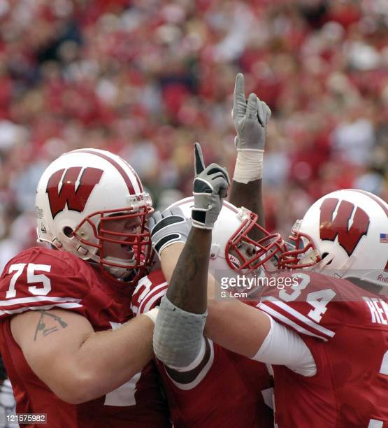 Wisconsin teammates Andy Kemp left and Bill Rentmeester right celebrate a touchdown by PJ Hill center during the game between the Wisconsin Badgers...
