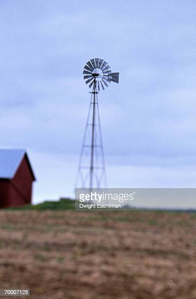 USA, Wisconsin, wind turbinel and barn, fields in foreground