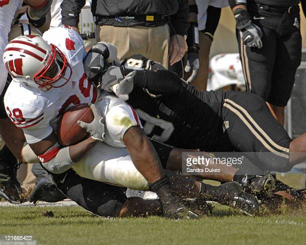Wisconsin's RB PJ Hill is brought down by Purdue's DE Anthony Spencer in the first half in Wisconsin's 243 win over Purdue in Ross Ade Stadium West...