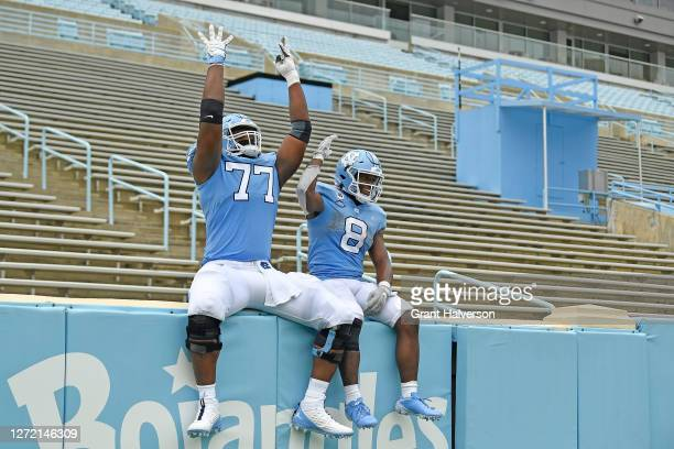 Wisdom Asaboro and Michael Carter of the North Carolina Tar Heels of the North Carolina Tar Heels jump into to the empty student section at the...