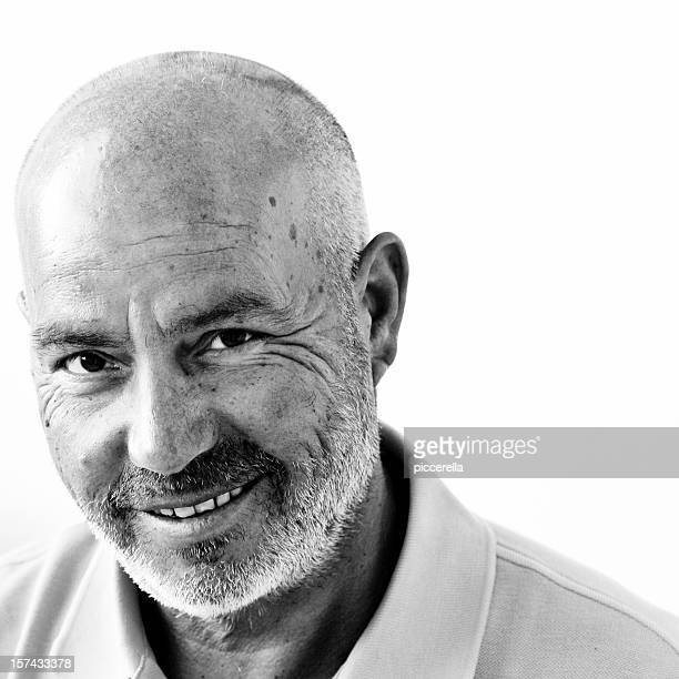 a wise bald happy man posing for a photo - zwart wit stockfoto's en -beelden