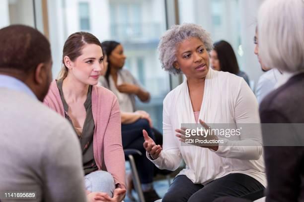 a wise mature woman shares with coworkers - piccolo gruppo di persone foto e immagini stock