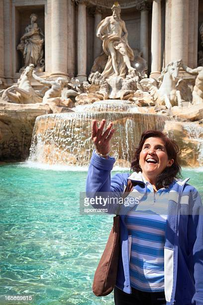 wishing - woman throwing coin into the trevi fountain rome - trevi fountain stock photos and pictures