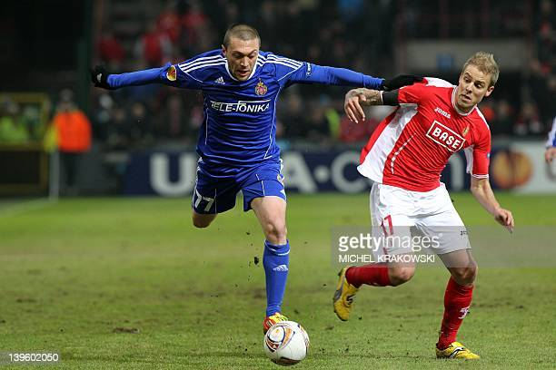 Wisla Krakow's Ivica Iliev vies with Standard de Liege's Yoni Buyens during the UEFA Europa League round of 16 second leg football match between...