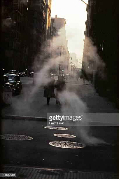 Wisps of steam drift down a New York street in the early morning