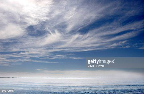 wispy clouds over a calm lake ontario - wispy stock photos and pictures