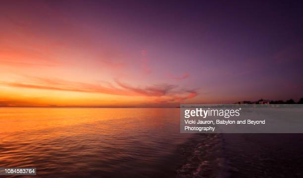 wispy pink clouds against sunset sky at fort myers beach, florida - gulf coast states photos et images de collection