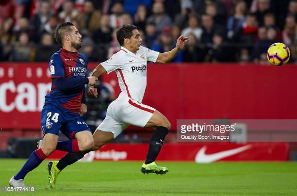 Wissam Ben Yedder of Sevilla competes for the ball with Jorge Miramon of Huesca during the La Liga match between Sevilla FC and SD Huesca at Estadio...