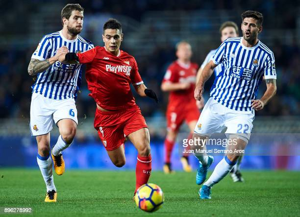 Wissam Ben Yedder of Sevilla FC being followed by Inigo Martinez of Real Sociedad and Raul Rodriguez Navas of Real Sociedad during the La Liga match...