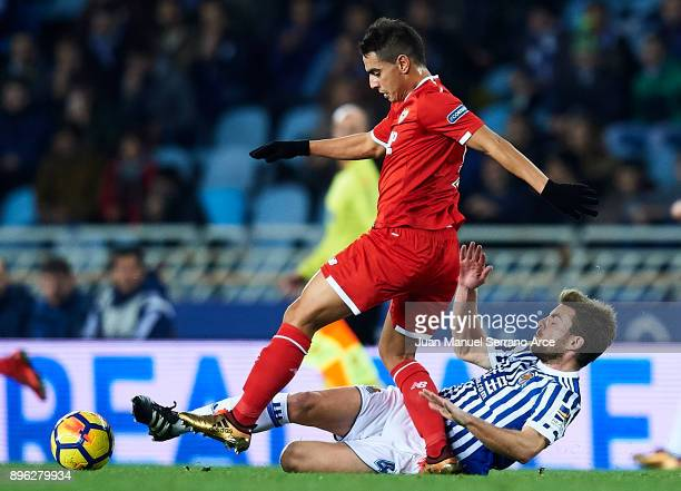 Wissam Ben Yedder of Sevilla FC competes for the ball with Asier Illarramendi of Real Sociedad during the La Liga match between Real Sociedad and...