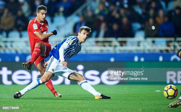 Wissam Ben Yedder of Sevilla FC shoots to score the first goal for Sevilla FC while is being followed by Diego Llorente of Real Sociedad during the...