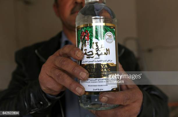 Wissam Ghanem an Iraqi man from the Yazidi community shows a bottle of the popular aniseflavoured spirit Arak at his shop in the town of Bashiqa some...