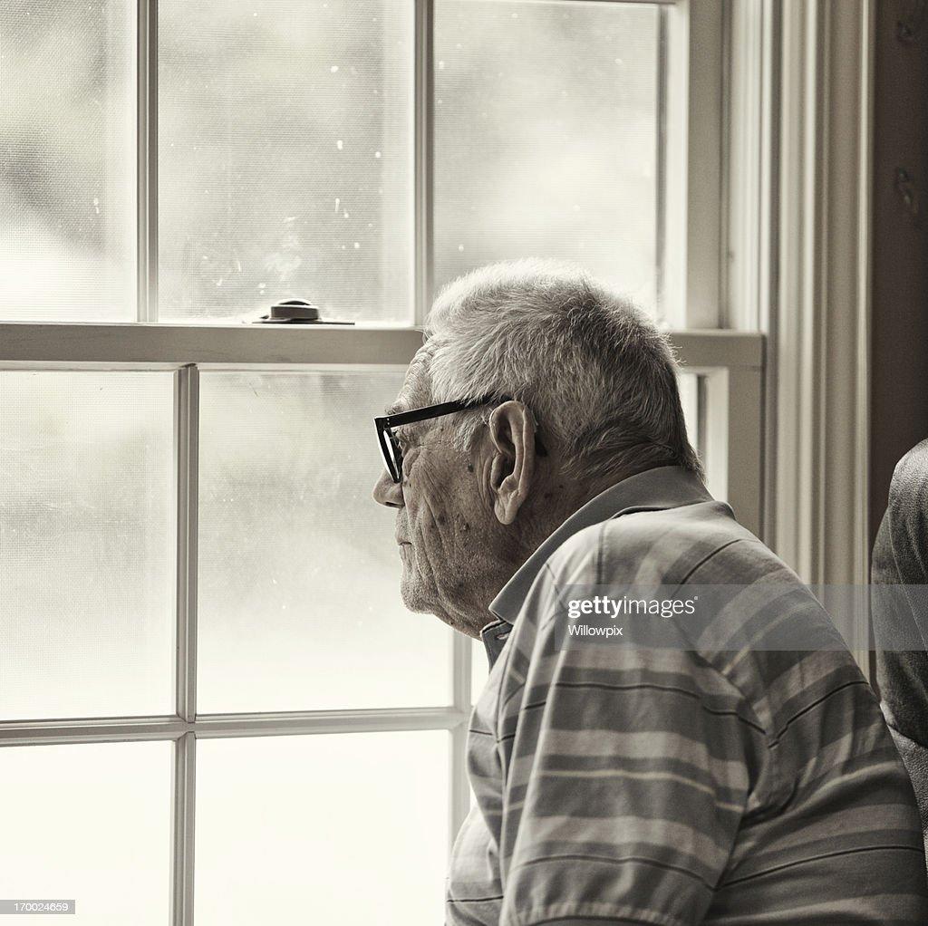 Wistful Senior Man Looking Through Grungy Window : Stock Photo