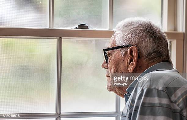 wistful senior man staring through hazy window - warzen stock-fotos und bilder