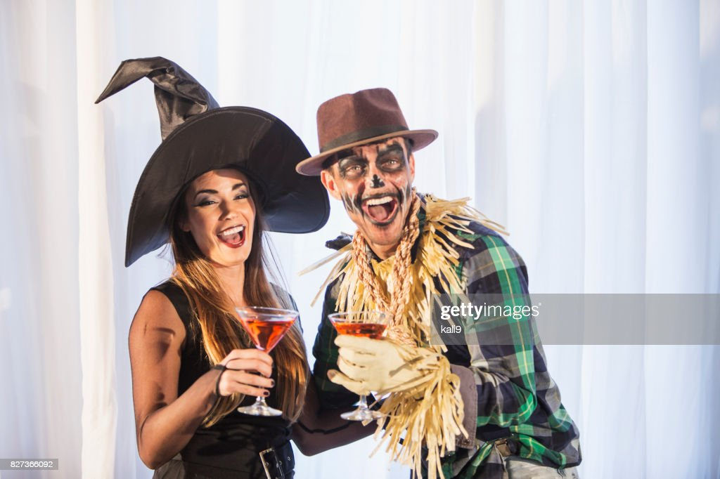 Witch and scarecrow at adult halloween party : Stock Photo