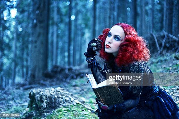 witch in the forest rading book. halloween theme - film poster stock pictures, royalty-free photos & images