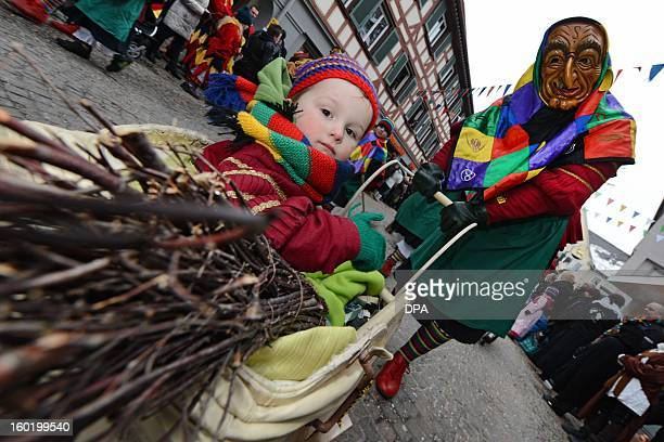 A witch of the Aulendorf fool guild pushes a child in a pram as she parades through the streets of Bad Saulgau southern Germany during the...