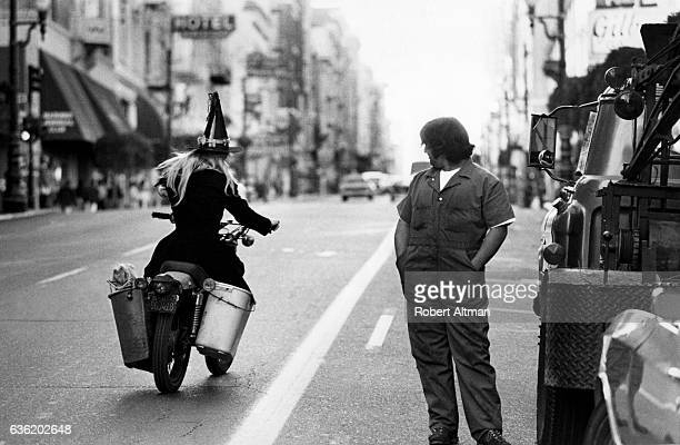 A witch rides on a Vespa down Sutter Street as a tow truck driver watches in October 1974 in San Francisco California