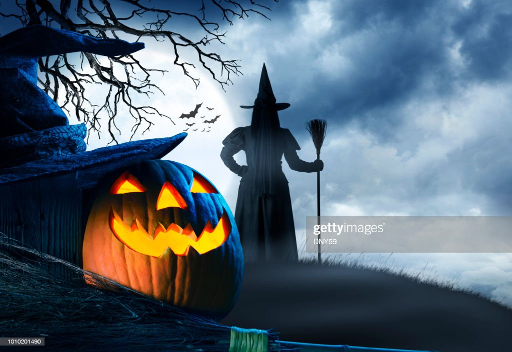 Witch Stands On Small Hill In Front Of Halloween Moon : Stock Photo