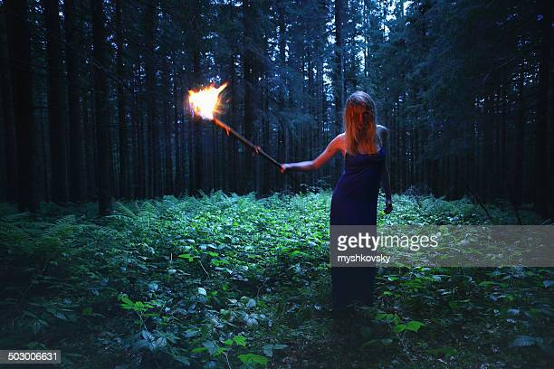 Witch with torch in evening dress