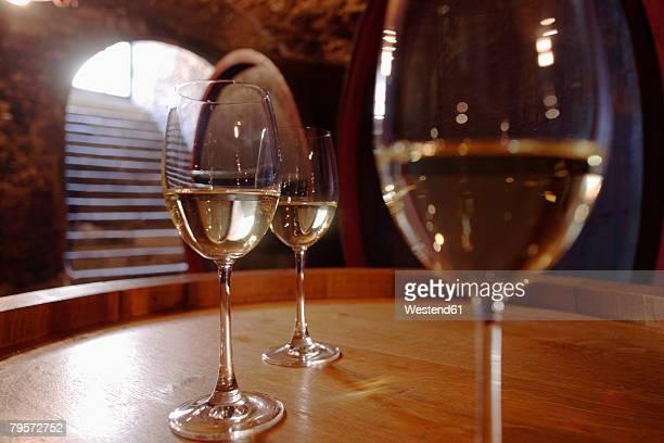 Wite wine in glasses on wine cask