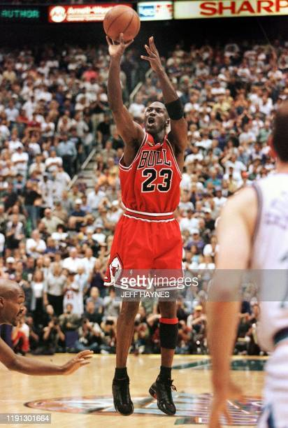 With 5.2 seconds left in the game Michael Jordan of the Chicago Bulls aims and shoots the game-winning jump shot as Bryon Russell of the Utah Jazz...