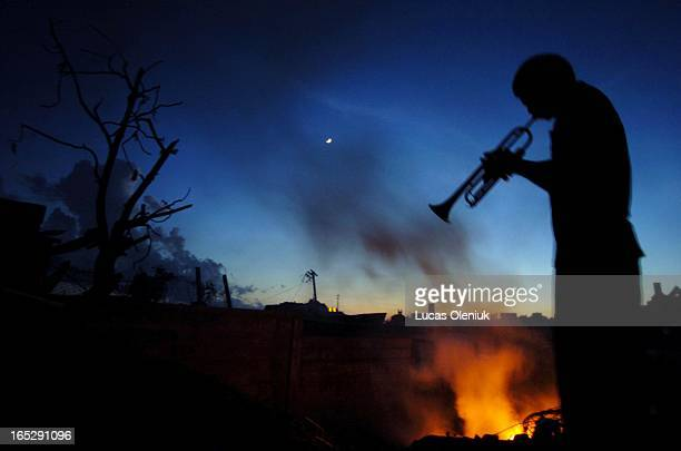 With a 6pm curfew instituted after severe looting in Grenada Garth Butcher fills the air with a sombre horn over top of the crackling burn of the...