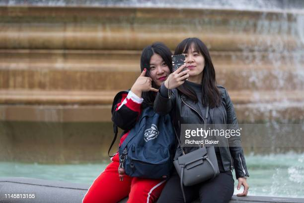 With a background of fountains two Asian friends take a selfie portrait with a mobile phone on which is the words Love You in Trafalgar Square on...