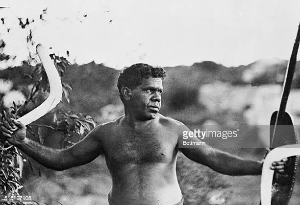 With a boomerang in one hand an Aborigine prepares to hurl another in the outbacks of Australia