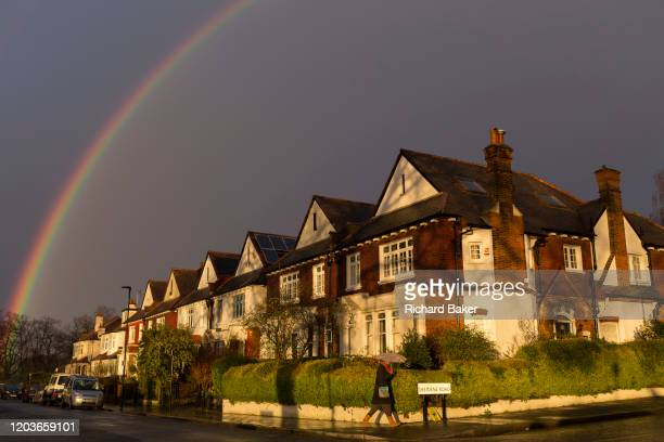 With a brief rainbow arcing overhead a pedestrian carrying an umbrella walks along a south London residential street passing sunlit Edwardian period...