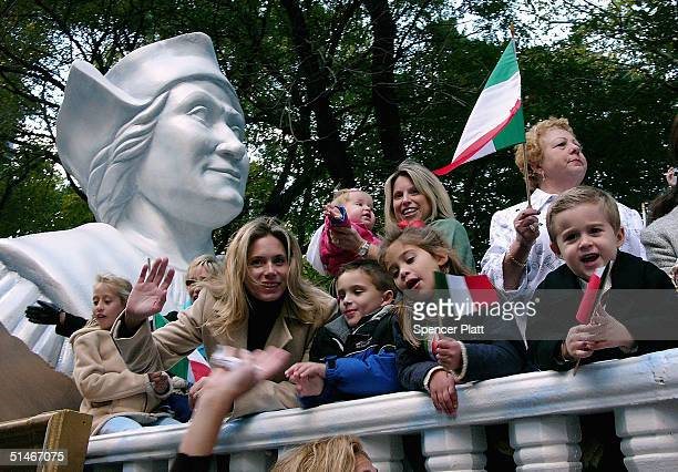 With a bust of Columbus behind them people wave Italian flags during the 60th annual Columbus Day Parade October 11 2004 in New York City Andretti...